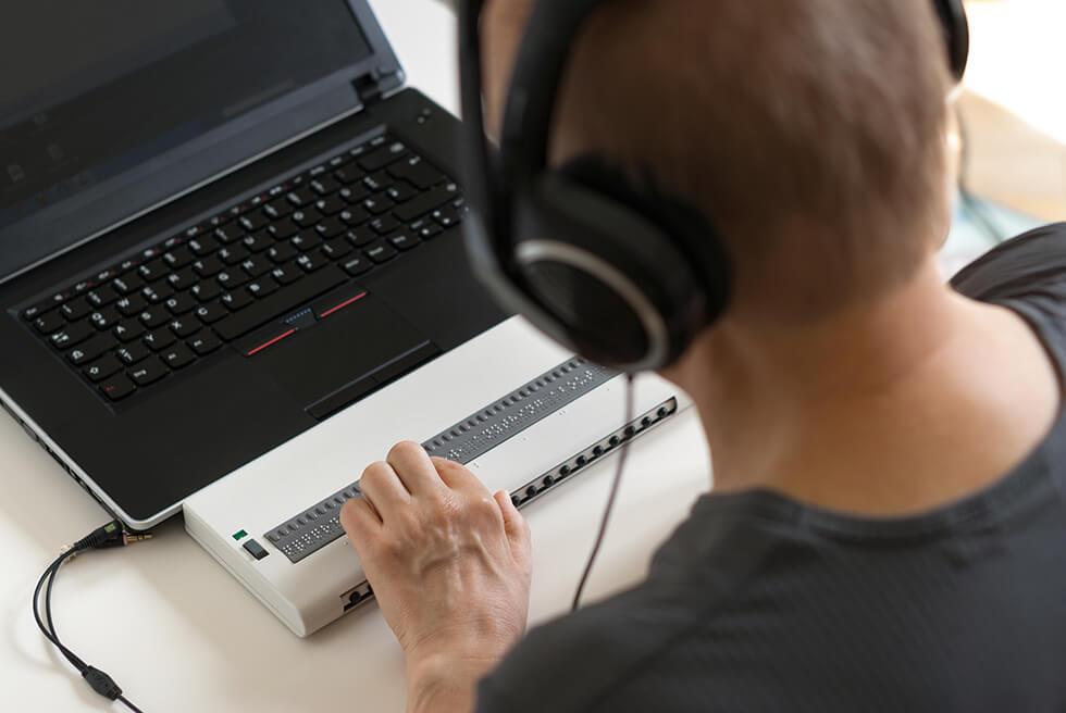 Persoon die werkt met een braille toetsenbord