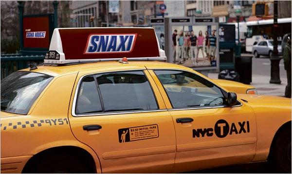 """voorbeeld woordgrappen in marketing. een gele taxi met een reclamebord bovenop waarop """"Snaxi"""" staat als het logo van Snickers."""